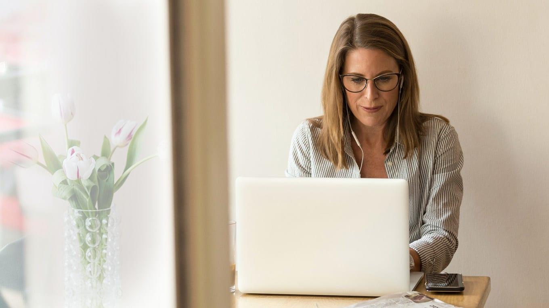 Frau um die 50 am Laptop absolviert erfolgreiches INQUA Coaching für späten Karriereeinstieg