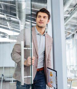 Junger Geschäftsmann öffnet Tür symbolisch für erfolgreichen Berufseinstieg