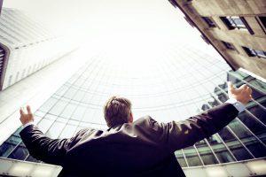 Älterer Geschäftsmann vor Firmengebäude, steht für erfolgreiche späte Karriere